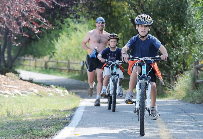 Tyler Trefethen, his brother PJ and father, John, make their way along the Yampa River Core Trail on Friday afternoon. Steamboat Springs recently was promoted to Bicycle Friendly Community gold status.