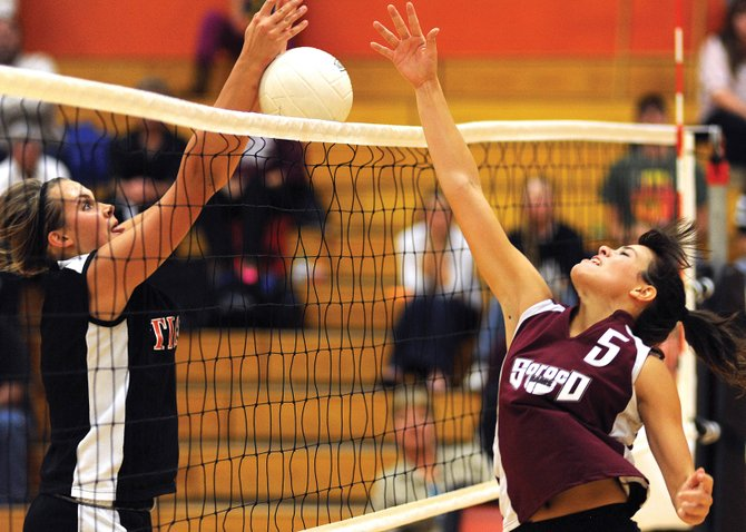 Soroco High Schools Mackenzie Carnahan tips the ball over the net as Haydens Erin Koehler tries to respond Friday. The Rams won more of the days at-the-net confrontations and, in the end, beat the Tigers in four games.