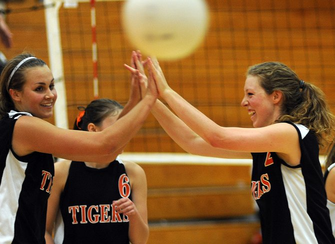 Hayden seniors Erin Koehler, left, and Aubree Haskins, right, celebrate after the final point in a five-game match victory against North Park. The Tigers bounced back from a defeat Friday against Soroco to split a doubleheader against North Park and Paonia.