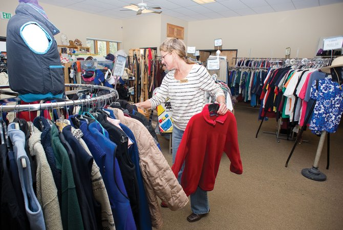 Susan Lupori, a volunteer with LIFT-UP of Routt County, sorts winter coats inside the thrift store Monday morning. It may be harder for some low-income families to keep warm this winter if  proposed cuts to the Low Income Energy Assistance Program take place. It would mean less funding for fewer families in Routt County. Department of Human Services Director Vickie Clark will recommends that people lower their thermostats and bundle up at home.