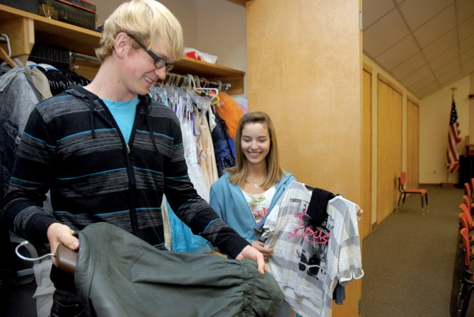 "Moffat County High School sophomores Dallen Gillett, left, and Caitlin Harjes examine 1980s-style outfits that may be used in the MCHS fall musical, ""Footloose,"" which is scheduled for November. Gillett and Harjes are cast as Willard Hewitt and Molly Lou, respectively. The performance will be ""a lot more strenuous than last year,"" Harjes said, but ""it's going to be fun."""