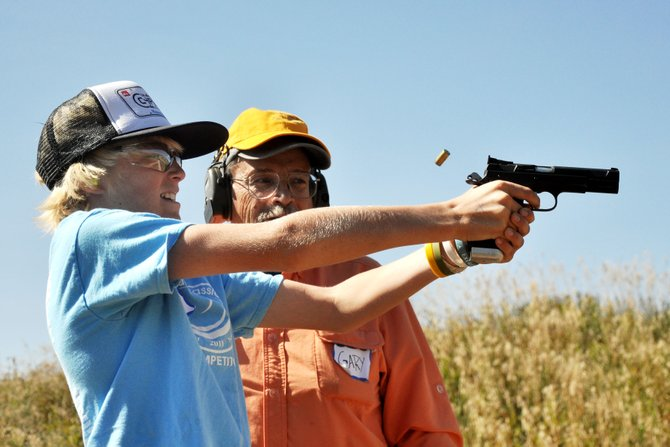 Gary Farrow watches 11-year-old Curtis Maltby fire a hand gun Sunday at the Lorna Farrow Memorial Fun Shoot at the Routt County Rifle Club. About 130 participants attended the 3rd annual event.