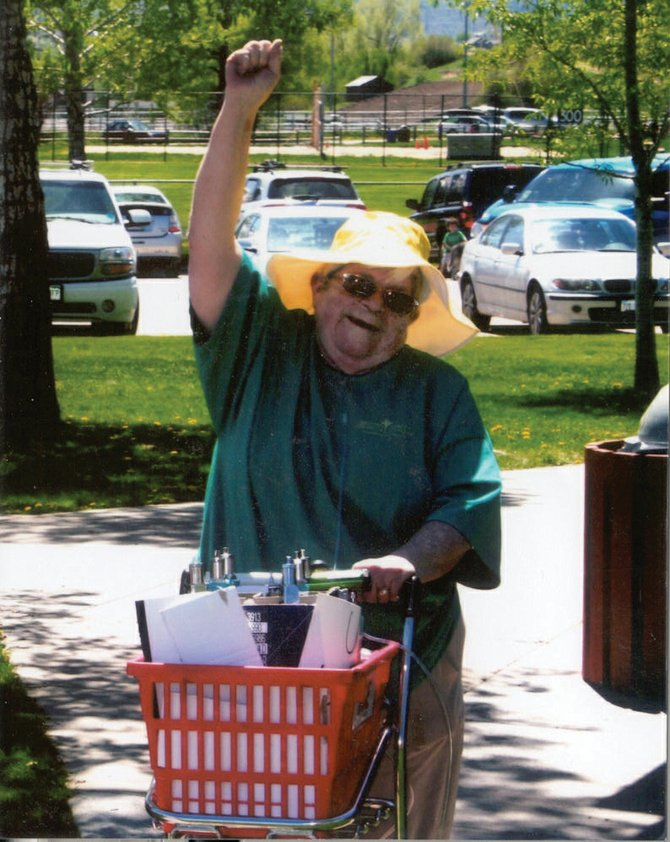 "Pushing a cart with six oxygen canisters, Martha ""Sam"" Van Horn, of Hayden, celebrates as she crosses the finish line of a 5K walk."