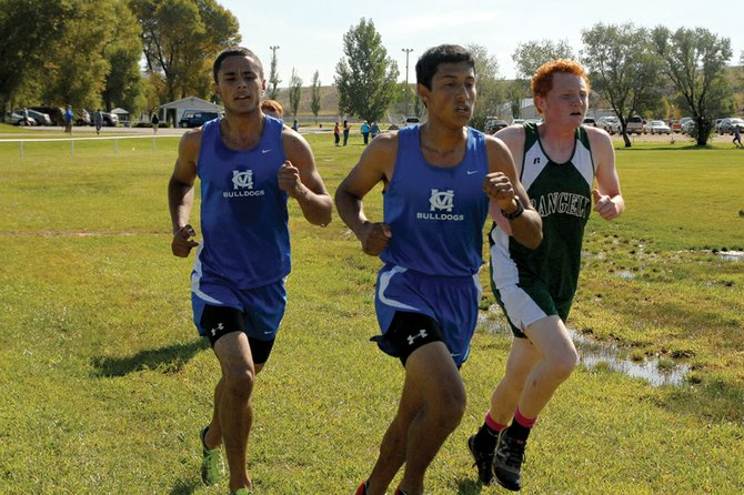 Moffat County High School seniors Rene Molina, middle, and Miguel Molina, left, try to fight off a Rangely runner Saturday during the MCHS Cross-Country Invitational at Loudy-Simpson Park. Rene and Miguel passed the Rangely athlete at the last second to take ninth and 10th, respectively, and help lead the boys team to a first-place finish.