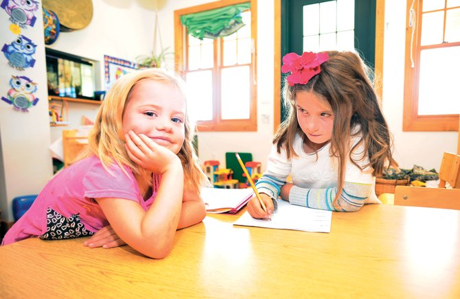 Preschooler Ellie Reynolds, left, shares a desk Monday with first-grader Ella Piret at North Routt Preschool. Piret, who spends her afternoons at the school as part of an afterschool program, and Reynolds returned to the school Monday after an unexpected closure last week.