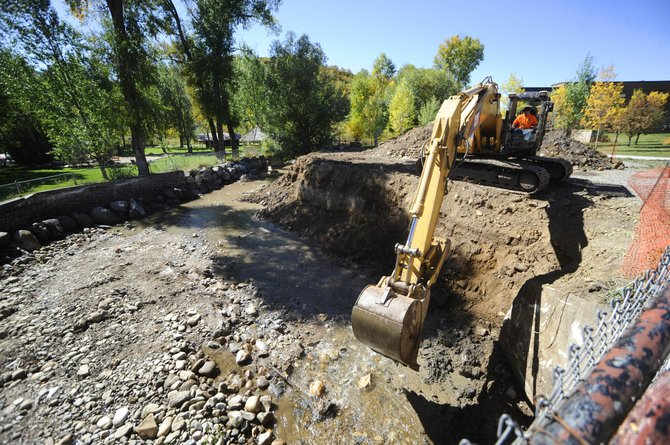 A track hoe is used to reconstruct the bank along Soda Creek on Tuesday where it flows past Lincoln Avenue next to Bud Werner Memorial Library.
