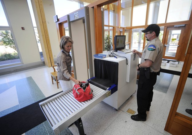 Routt County Sheriff's Office Deputy Blaine Watson screens Routt County Justice Center employee Rene Mattone's bag on Tuesday. The Sheriff's Office is testing the new screening machine as a way to avoid searching bags by hand.