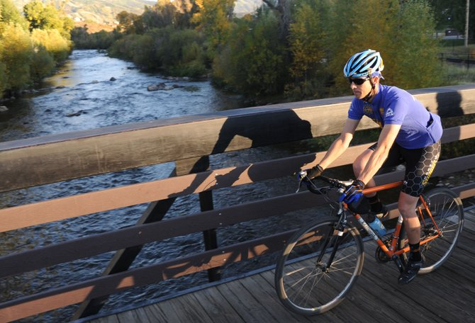 J.R. Thompson rides across a Yampa River bridge on the Yampa River Core Trail on Wednesday evening in Steamboat Springs. The second annual Steamboat Springs Bike Summit returns this weekend. The four-day event starts tonight with a speaker and a documentary screening and wraps up Sunday morning with a downhill mountain bike race at Steamboat Ski Area.