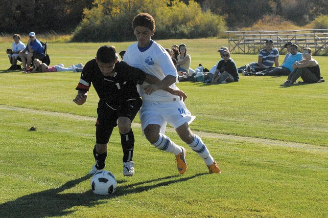 Alan Flores, a Moffat County High School junior, battles an Eagle Valley High School defender Thursday at Loudy-Simpson Park. The Bulldogs trailed 2-1 at half time, but rallied back to win, 4-2.