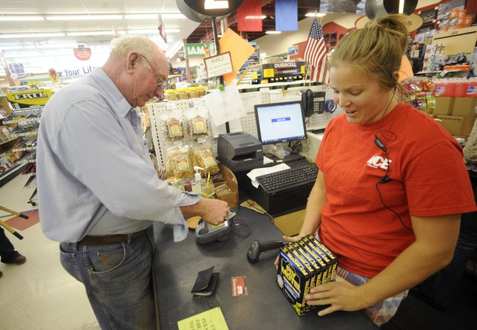 Ace at the Curve cashier Emily Fisken bags Jimmy Callahan&#39;s purchases as he pays with plastic Friday.