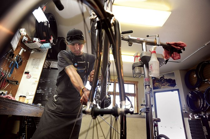 Eric Hockman, a bike mechanic for Steamboat Ski & Bike Kare, works on a wheel at the downtown shop Monday afternoon. The bike store enjoyed one of it's best months in August and the employees think the USA Pro Cycling Challenge played a part in the shop's success.