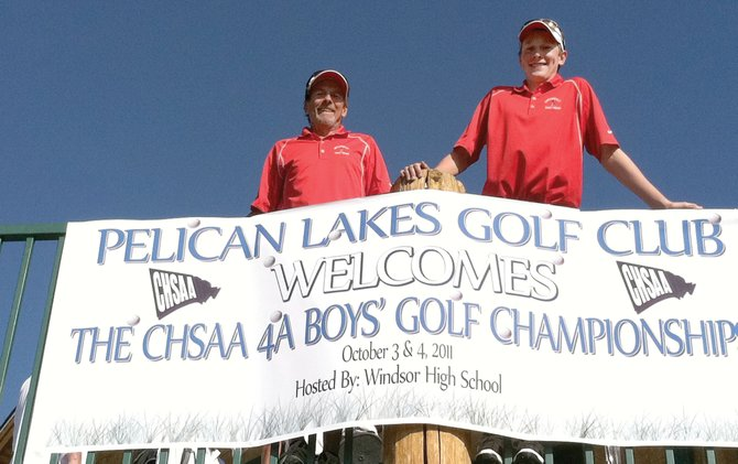 Steamboat Springs High School golf coach Steve Dodson, left, and sophomore Erik Sobeck stand in front of a banner at the Pelican Lakes Golf Club in Windsor during the 2011 state high school golf championships.