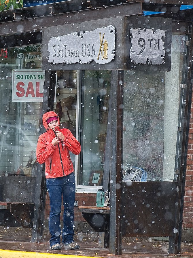 Laraine Martin zips up her coat while waiting for the bus in the snow at the Ninth Street stop on Lincoln Avenue in downtown Steamboat Springs. A storm brought the first signs of winter to the area Thursday.