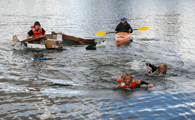 "Spencer Hebert, left, continues to paddle while teammates Katelyn Sollenberger, front, and Nicole Sollenberger swim for shore and Moffat County High School teacher Eric Hansen looks on Friday afternoon during the cardboard boat regatta at Loudy-Simpson Park. Hebert said he intended for his boat, named ""Titanic II,"" to sink."