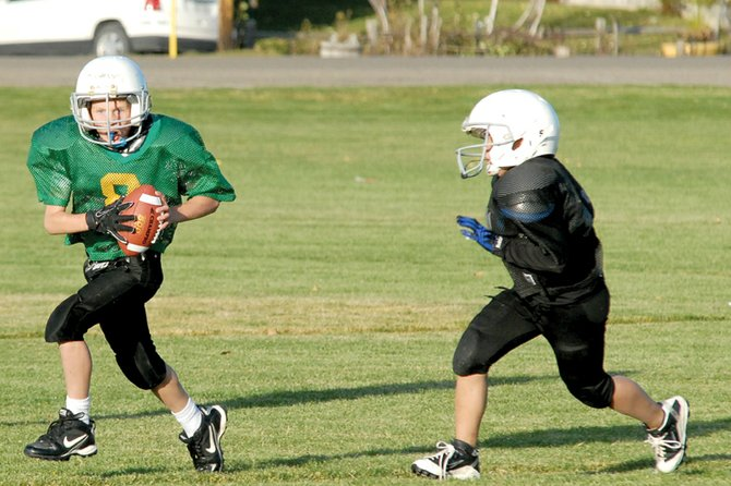 The Packers' Chris Scherbarth breaks out of the pocket Wednesday at Woodbury Sports Complex during the Doak Walker third- and fourth-grade football championship game. Scherbarth had a score on the ground and through the air to help lead the Packers to a 21-7 victory and a perfect 9-0 record.
