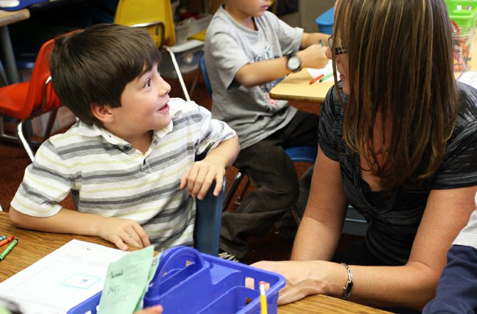 """First-grader Ian Trevenen, left, tells Lori Gowdy, loan administration specialist for First National Bank of the Rockies, about how much money he has Wednesday afternoon in his classroom at East Elementary School. Trevenen and other students in Alegra Corey's first-grade class learned about safe places to store their money during an installment of the """"Teach Children to Save"""" program offered by the bank's Craig branch."""