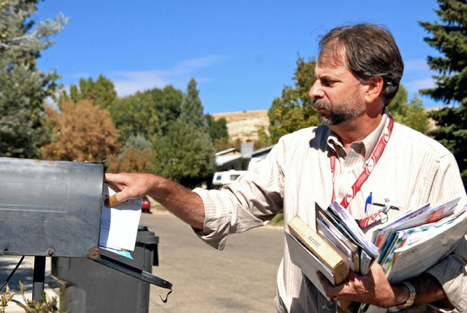 Craig Postmaster Clifford Carter delivers mail on what has become one of his usual routes. Carter has lost a carrier to retirement and another to sick leave since taking over the post office last year, but is pitching in to maintain delivery service.