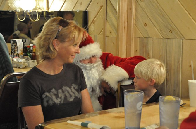 Debbie Montgomery and son, Logan, 8, chat with Santa Claus during the Christmas for Kids fundraiser Saturday at the Golden Cavvy, 538 Yampa Ave. The Montgomery family was one of many groups of customers who donated to the charitable effort that featured numerous volunteers serving patrons throughout the day.