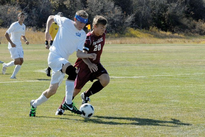 Bryant Cox, a Moffat County High School junior, fights off a Palisade defender Saturday at Loudy-Simpson Park. The MCHS boys varsity soccer team scored early and often in an 8-0 victory.