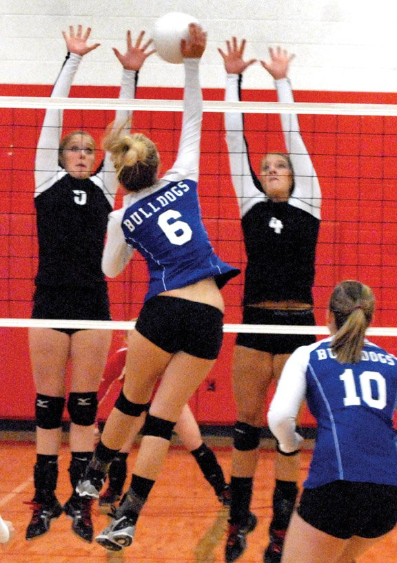 Moffat County High School junior Makayla Camilletti spikes one past Glenwood Springs Demons Kenzie Nelson-Buehler, left, and Lexie Warkentin in Saturday's games in Glenwood Springs. The Bulldogs fell in three straight sets.