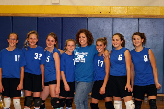 Coach Cristy Simpson, center, celebrates with her Craig Middle School seventh-grade volleyball A-team players Saturday. The players from left, are Josey King, Mattie Jo Duzik, Tashiena McElhinney, Emma Samuelson, Alex Hamilton, Sidney Ferguson and Christa Bird. The team won the district championship Saturday afternoon, beating Rangely 2-0 in the final round to finish the season 9-3.