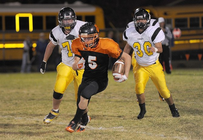Hayden's Ryan Domson runs past the Meeker defense in the first half of Friday night's football game in Hayden.