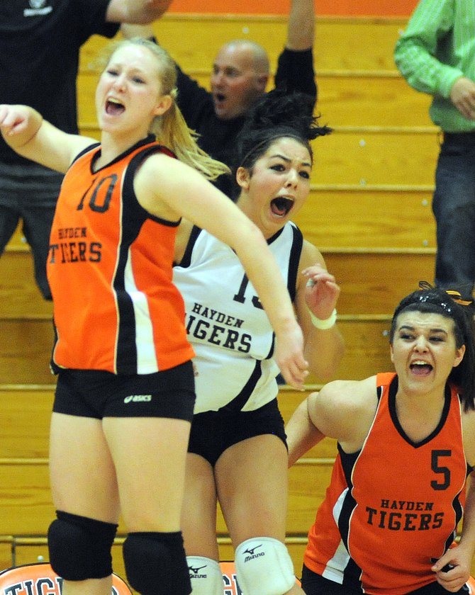 The Hayden High School girls volleyball team erupts Saturday after the final point in the Tigers' five-game upset victory against Vail Christian.