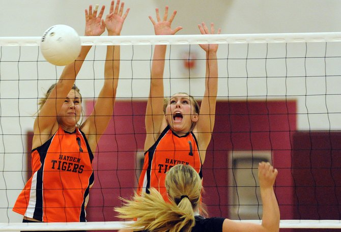 Hayden's Erin Koehler, left, and Brette Frentress pick up a block Saturday during the district volleyball tournament in Oak Creek. The Tigers were at their best late, winning a thrilling five-set match against Paonia, but they were inconsistent in a pair of earlier matches against Meeker and Rangely.
