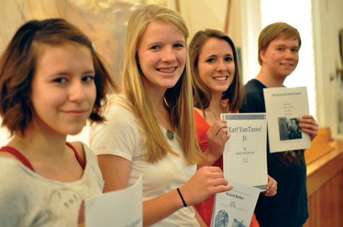 From left, Moffat County High School juniors Abby Landa, Rose Howe, Faith Santistevan and Skyler Gerini pose in the Museum of Northwest Colorado on Wednesday, holding the biographies they wrote about Moffat County residents this spring. They were chosen to donate their works to the museum, and additional copies of their report will also go to Wyman Museum, the Moffat County Library and the MCHS library.