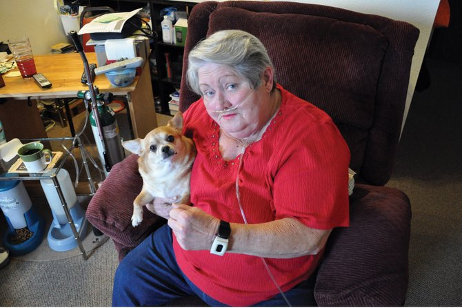 Darlene Turner displays the Lifeline personal help button she wears on her wrist at her home in Sunset Meadows II on Friday. Turner, pictured here with her Chihuahua, Cash, has used the device for four years and says it has given her a sense of security while helping her maintain her independence.
