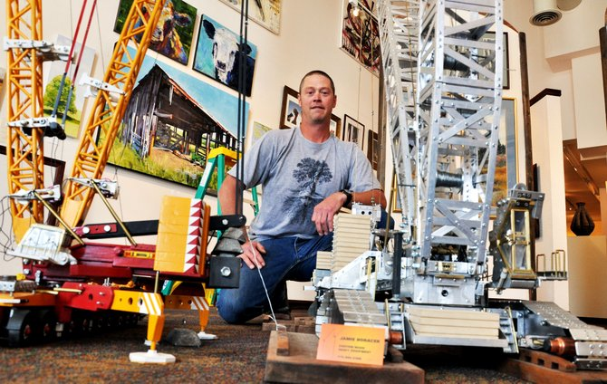 Jamie Horacek stands next to the scale model cranes he built in his Stagecoach home. Horacek's cranes will be on display this month at the Steamboat Springs Center for Visual Arts, and he will demonstrate how they work from noon to 5 p.m. Sundays.
