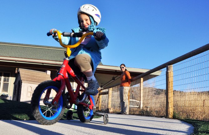 North Routt Preschool student Emma Crocker rides her bike Thursday during recess as her mother, Kerri Ann Crocker, looks on. Kerri Ann Crocker started as the school's new director Oct. 31.