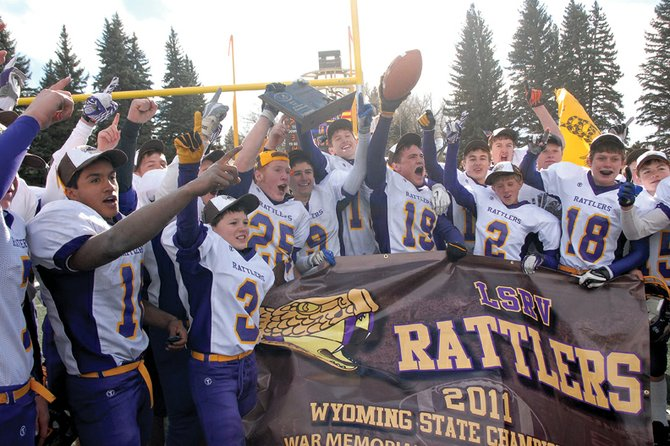 The Little Snake River Valley School six-man varsity football team celebrates Saturday in Laramie, Wyo., after capturing the team's second straight Wyoming 1A six-man state title with a 54-33 victory over Dubois. The Rattlers' victory capped off a perfect 11-0 season.