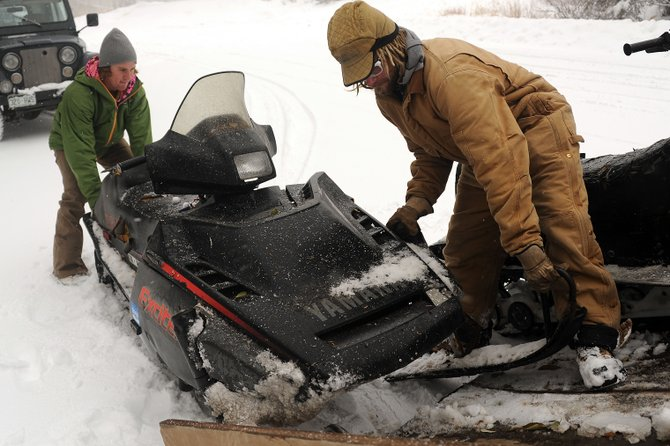 Alex Sullivan, left, and Kerry Lofy unload a snowmobile Sunday at Dry Lake Campground.