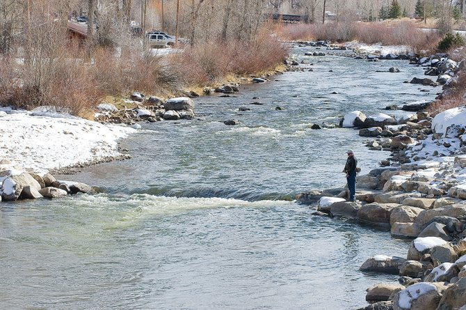 Steamboat Springs fisherman Dan Brabec takes advantage of Friday's mild weather to hang out on the banks of the Yampa River downtown. A storm is expected to bring cooler weather and snow to the area this weekend.