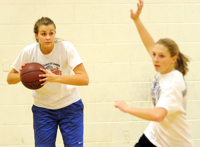 Hayden senior Erin Koehler looks for a pass Thursday as Savannah Williams cuts through the lane while the girls basketball team worked on its half-court motion offense. The team, state tournament qualifiers two of the past three years, begins its season Dec. 1.