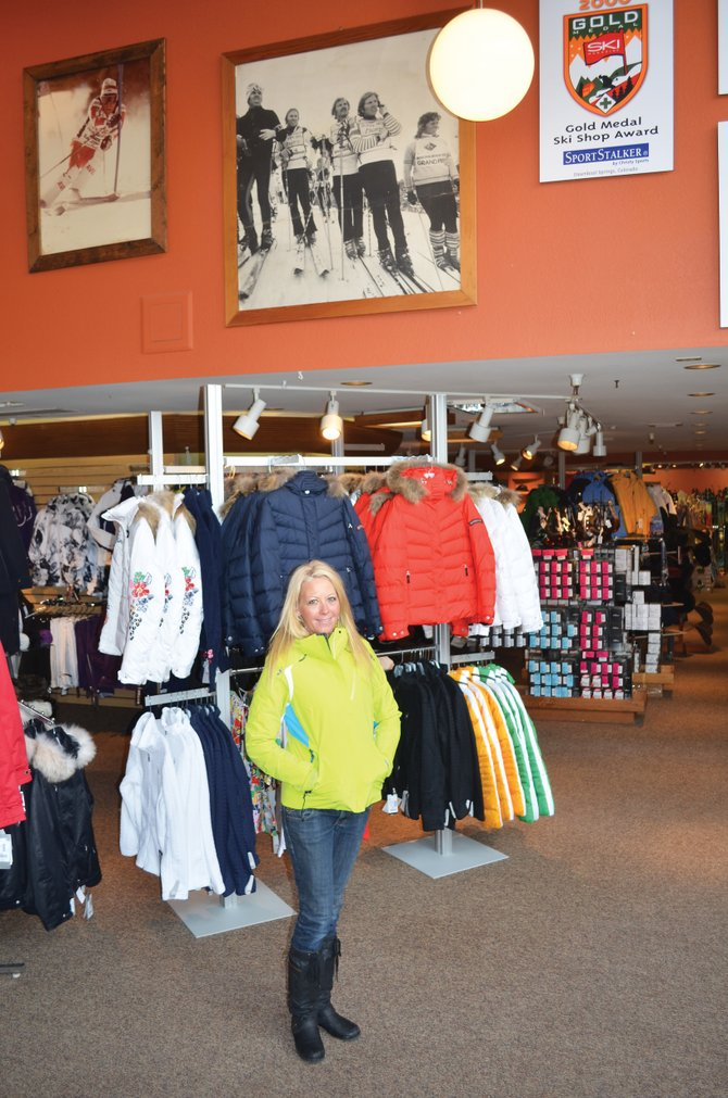 Gina Grether, soft-goods manager at the SportStalker store, models a Descente ski jacket at the entrance to the shop in Gondola Square that is a flagship location for Christy Sports.  The shops name changes to Christy Sports on Monday.