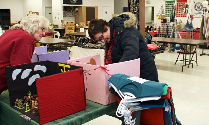 "Norma Henderson, of Craig, left, shows Tammie Hanel, of Craig, her ""fold and go play stations"" Saturday during the craft sale at Veterans of Foreign Wars Post 4265. Hanel said she prefers to give locally made, hand-crafted gifts during the holidays ""because I know what kind of work goes into it."""