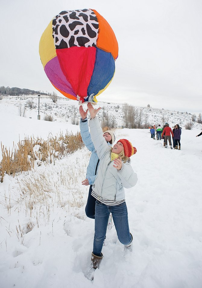 Sixth-graders Lauren Graham, front, and Esté Wilkinson chase the balloon they created in science class as it comes to a soft landing at the Steamboat Springs Middle School football field Monday morning. The balloon launch, which involves filling the colorful paper balloons created by students in science class with heated air, is an annual event at the school in which students learn about convection.