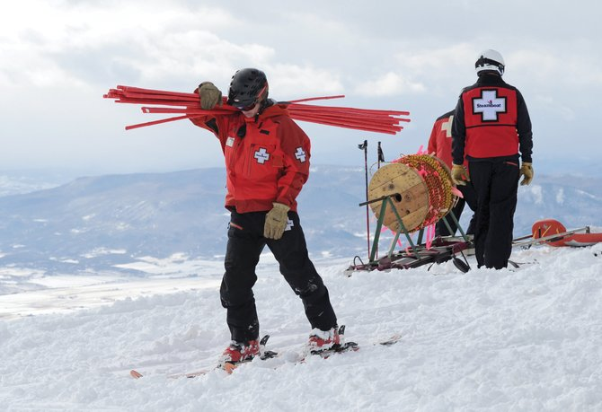 Steamboat Ski Patrol memeber Matt Piva heads out with a armload of bamboo as the Steamboat Ski Area begins roping and padding areas on the mountain in preparation of the resort opening Wednesday for Scholarship Day. 