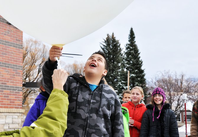 Soda Creek Elementary School fifth-grader Brian Arias admires a weather balloon Tuesday morning held by National Center for Atmospheric Research scientist Bill Brown.