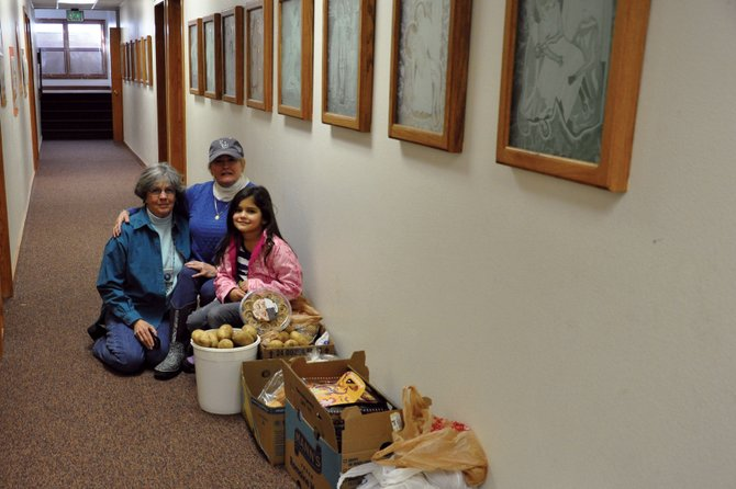 St. Michael's Community Kitchen volunteers, From left, Delaine Voloshin and Della Baldwin pose with Voloshin's granddaughter, Isabella Sanchez, near potatoes and other food donated to the kitchen for its Thanksgiving meal Thursday. The kitchen served Thanksgiving meals to about 180 people last year, including homebound residents who had meals delivered to them, volunteer Robin Schiffbauer said.