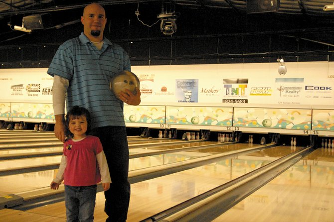 Craig resident Daniel Curtis stands with his daughter, Joslyn, on Monday at Thunder Rolls Bowling Center. Curtis bowled a perfect 300 game Nov. 6 during Sunday Night Mixed league play.