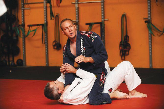 Nate Daughenbaugh demonstrates a choke move on Dave Marrs during Brazilian Jiu-Jitsu training in Steamboat Springs.