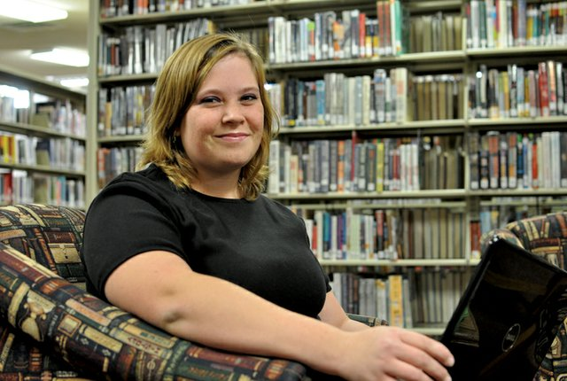 Bethany Longwell, 20, of Craig, poses in the Moffat County Library in Craig with the laptop she uses to write her novel for National Novel Writing Month. This is the first year Longwell is participating in the annual event, which takes place every November and challenges authors to write a 50,000-word novel in a month.