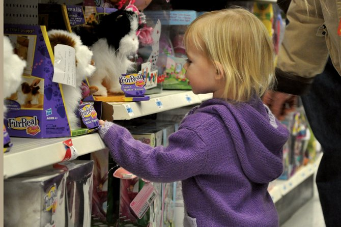 Sadie Morris, 2, of Steamboat Springs, examines a toy Friday morning at Kmart in Craig . Although Black Friday alone doesn't carry a major share of the store's profits, the final quarter of the year — which includes October, November and December — accounts for about a quarter of its annual sales, store manager Cody Ransberger said.