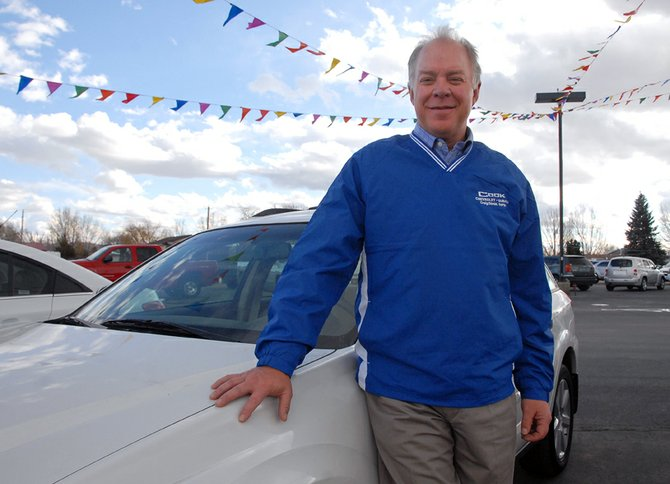 Scott Cook, owner of Cook Chevrolet and Subaru, stands Friday with a Subaru Outback, the dealership's best-selling model, at the dealership's Craig branch on West Victory Way. Cook said because of his love for the outdoors, he never anticipated joining the family car business. But, he eventually fell in love with the work after graduating from Colorado State University in 1979 with a degree in business management.