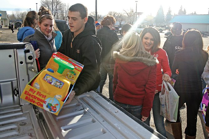 Brentt Gabel, of Hayden High School, places a toy in the back of a truck during last year's KRAI Holiday Drive. This year's event is scheduled for 6 a.m. to 6 p.m. Thursday and Friday at Centennial Mall, 1111 W. Victory Way.