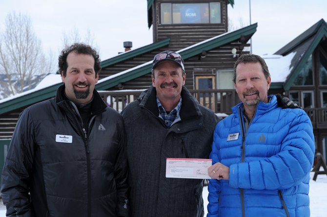 Steamboat Ski and Resort Corp. Senior Vice President of Sales and Marketing Rob Perlman, left, and Vice President of Skier Services Jim Schneider, right, present Steamboat Springs Winter Sports Club Executive Director Rick DeVos with a check for $63,445 from Scholarship Day.