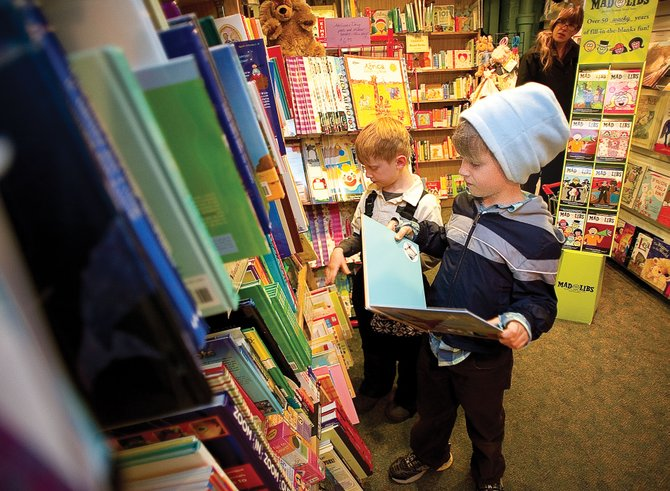 Twins Michael, front, and Noah Robinson, 7, shop with their mom, Jennifer, at Off the Beaten Path Bookstore in downtown Steamboat Springs. Off the Beaten Path is one of 57 stores participating in the holiday shopper reward program.